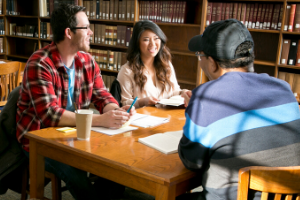 Students in library talk and interact