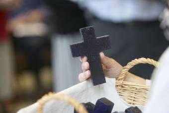 student holds blue glass cross