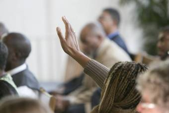 Worshiper raises a hand up during service in Goodson Chapel