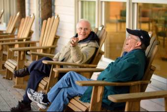 Two pastors sitting on a porch talk and laugh