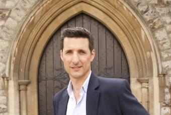 Professor Luke Bretherton poses in Duke Chapel archway