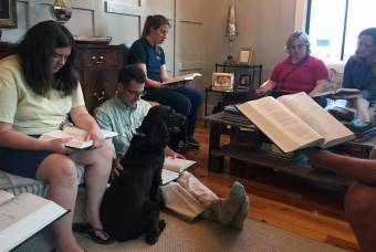 A prayer gathering of Friendship House in Fayetteville, N.C. Scott Cameron sits on the floor beside his dog.