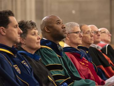 Faculty sit in academic robes in Duke Chapel