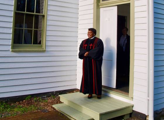 A minister stands at the doorway of a church