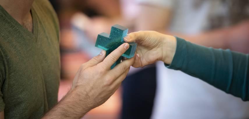 hands pass glass cross during worship service