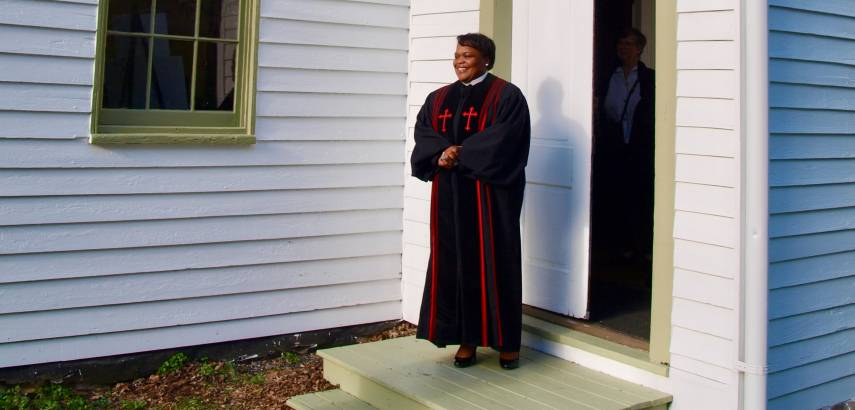 preacher stands at church doorway