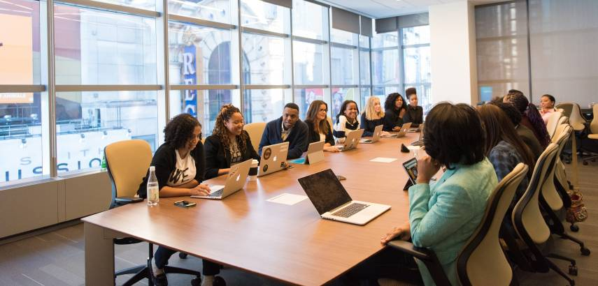 Professionals gather around a conference table that overlooks a city scene