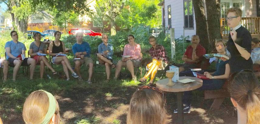 a preacher and students have a discussion outdoors